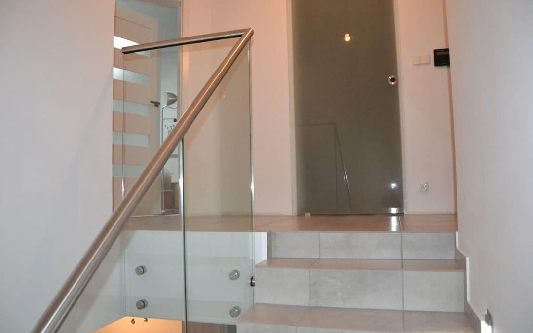 Szklana balustrada mocowana punktowo z metalową poręczą